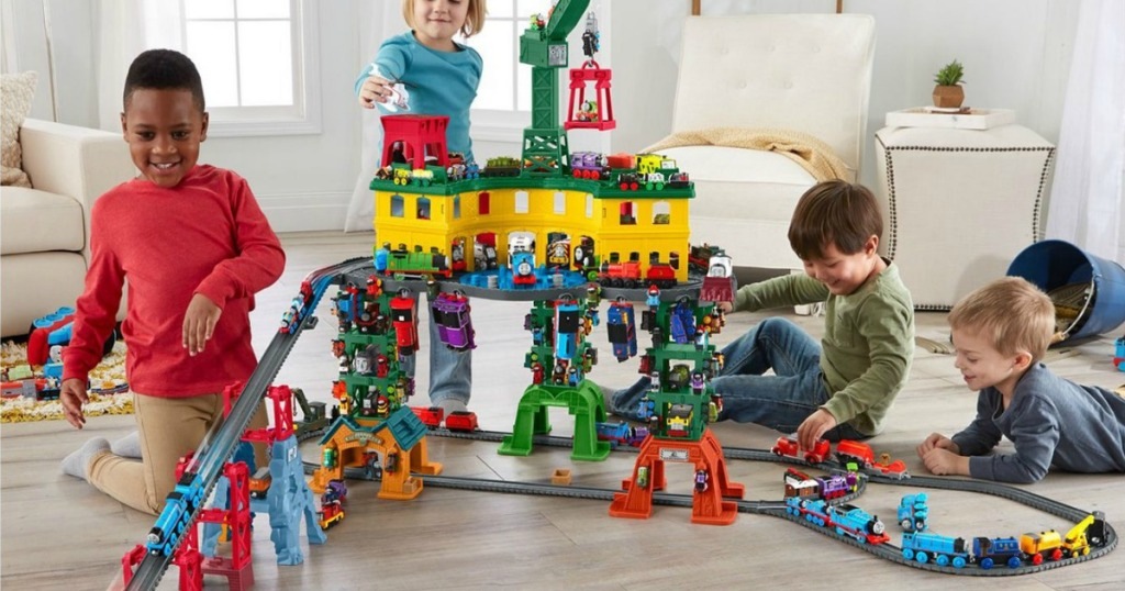Four young boys playing with a large Thomas and Friends Train Station set