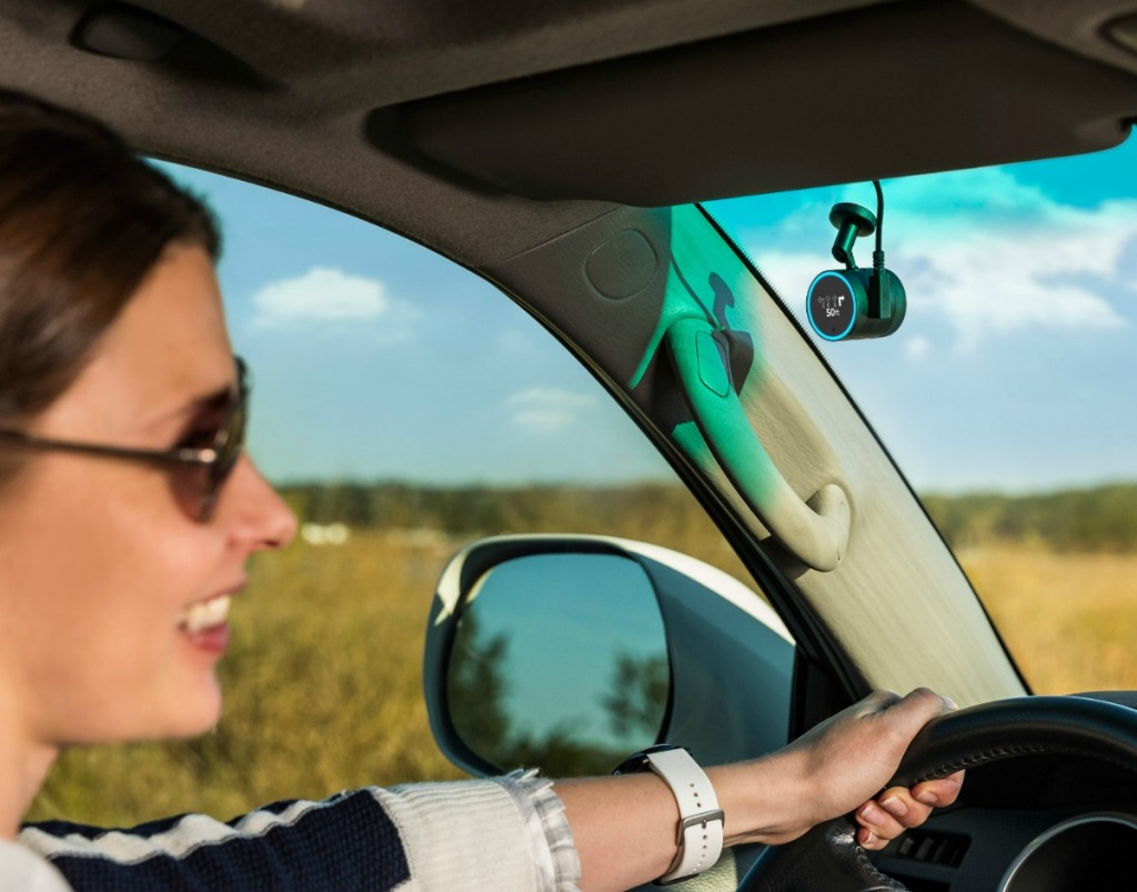 Woman driving car with GPS on windshield