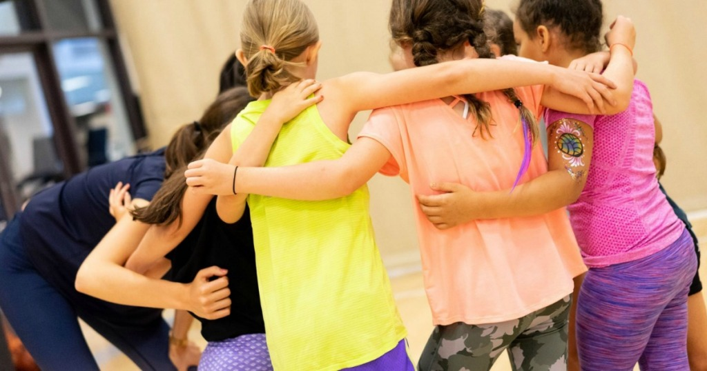 Girls wearing Athleta shirts in gymnasium
