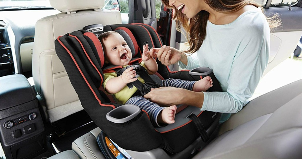 Woman fastening baby into Graco car seat
