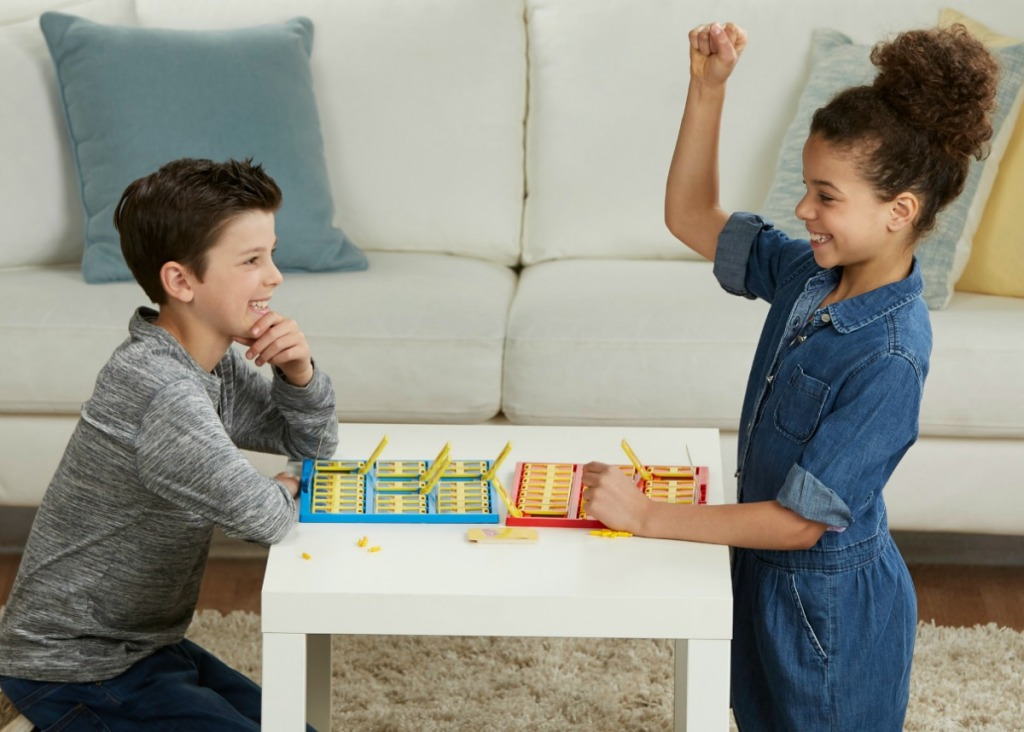 boy and girl playing Guess Who? game at small table
