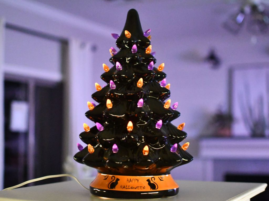 Lit up Halloween Tree in room with purple lighting
