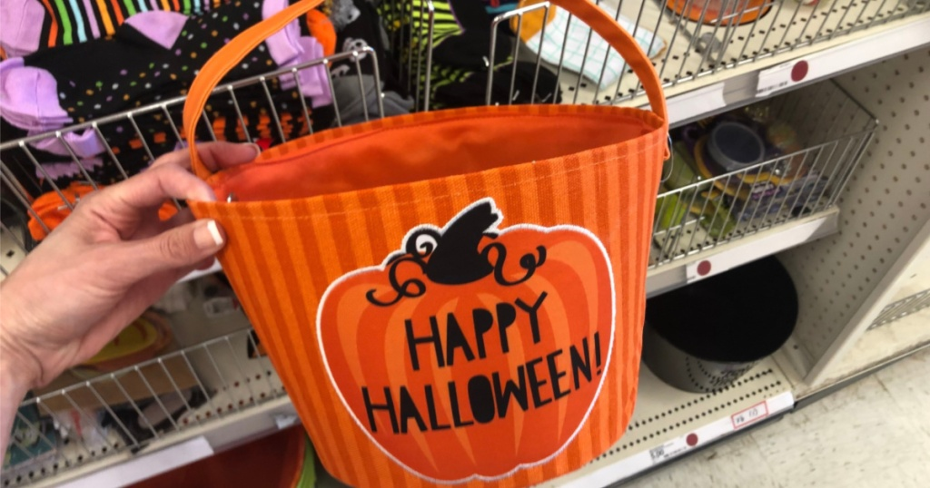 woman holding up halloween candy bucket at target