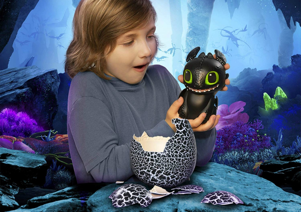 boy holding Hatching Toothless Interactive Baby Dragon