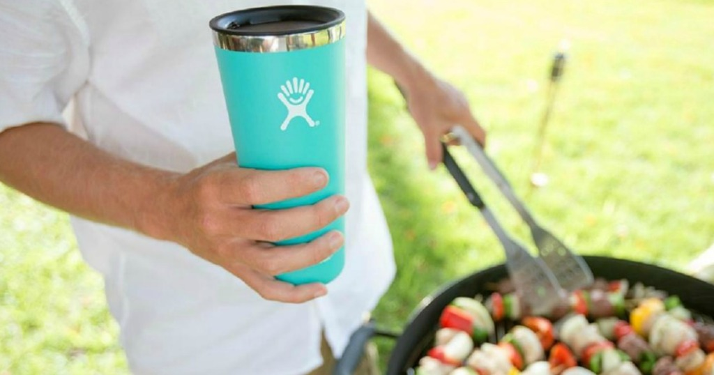 man holding a Hydro Flask and grilling outdoors