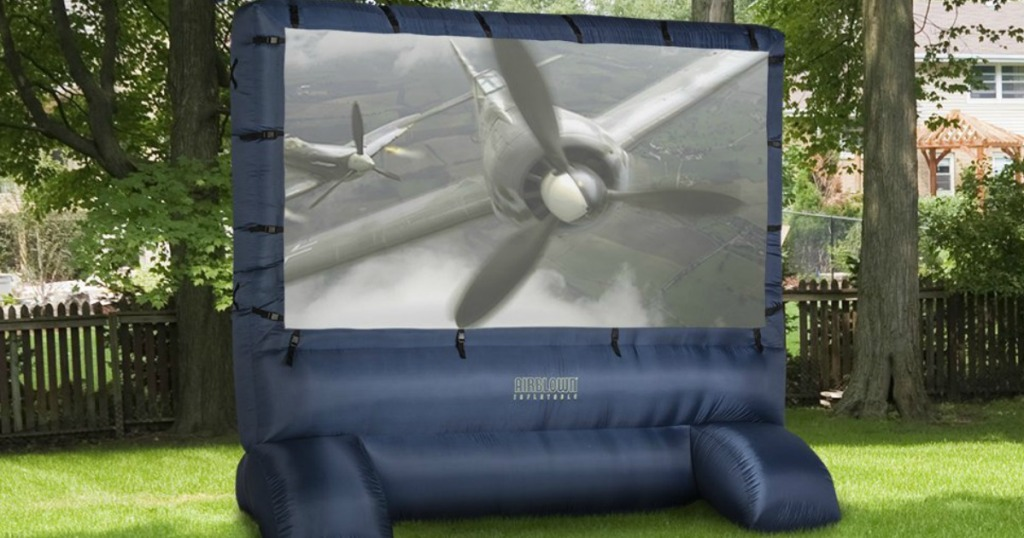Large dark blue inflatable movie screen with plane image on screen outdoors