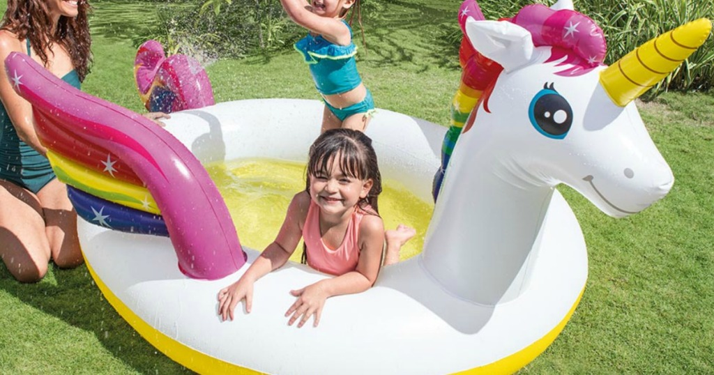 Unicorn themed pool in backyard with kids and mom playing