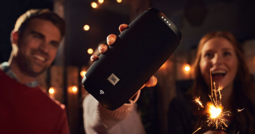 hand holding JBL LINK 10 Portable Bluetooth Speaker with people in the background and sparklers