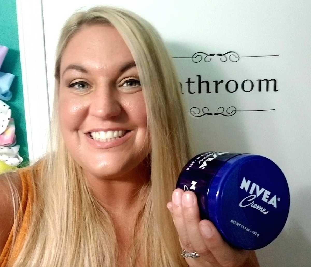 woman holding blue jar of NIVEA creme