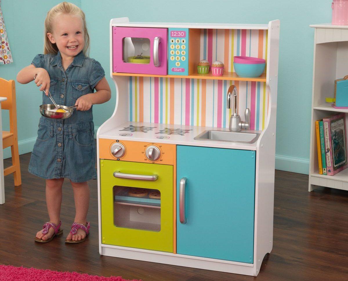 child next to toy kitchen