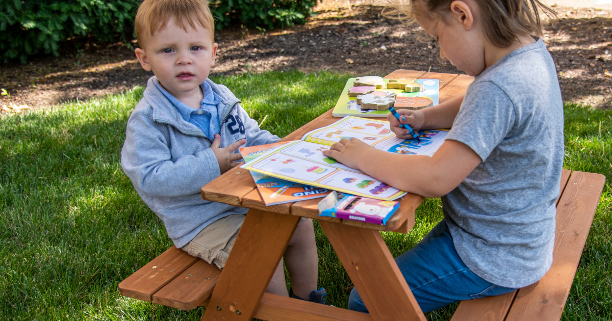 kids sitting at picnic table with books