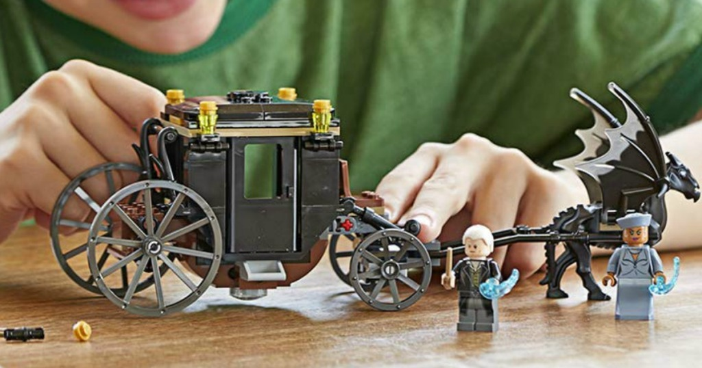boy playing with LEGO Fantastic Beasts Grindelwald's carriage set