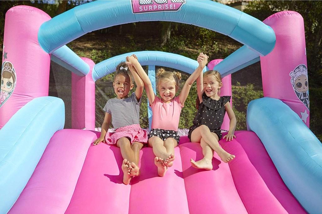 girls sliding down slide on LOL Surprise Bounce House