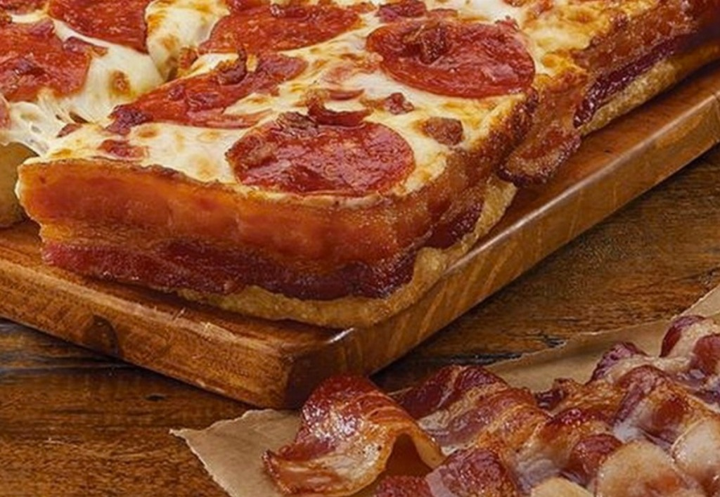 Close up view of a bacon wrapped deep dish pizza