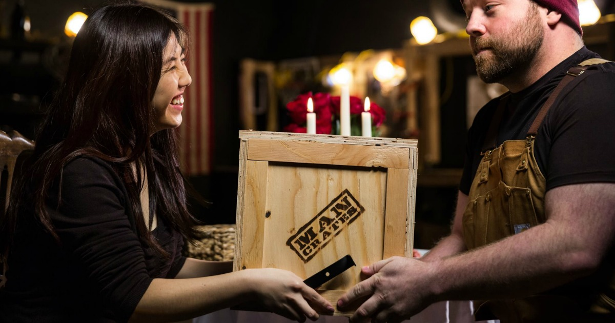 Woman gifting Man Crate to man during candlelight dinner
