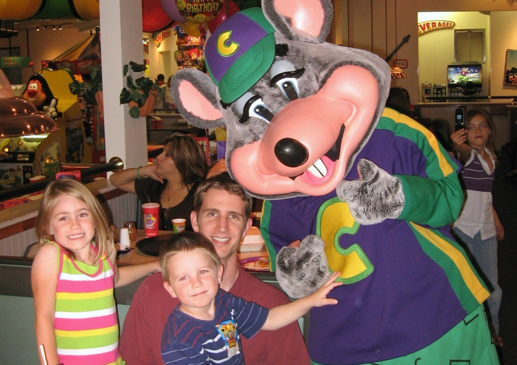 family sitting next to mouse at Chuck E. Cheese