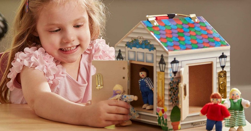 girl playing with doll in dollhouse