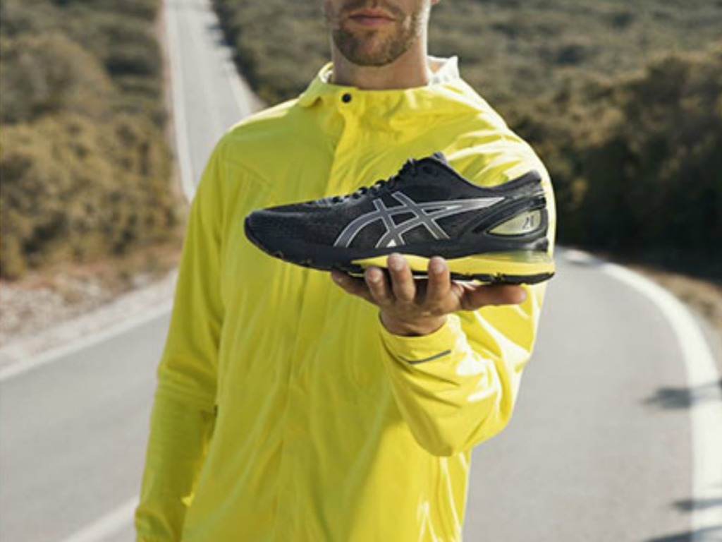 man holding yellow and black shoes with road behind him