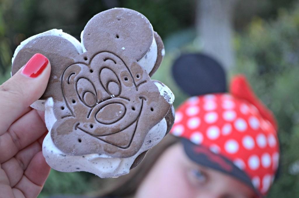 girl holding up Mickey ice cream sandwich