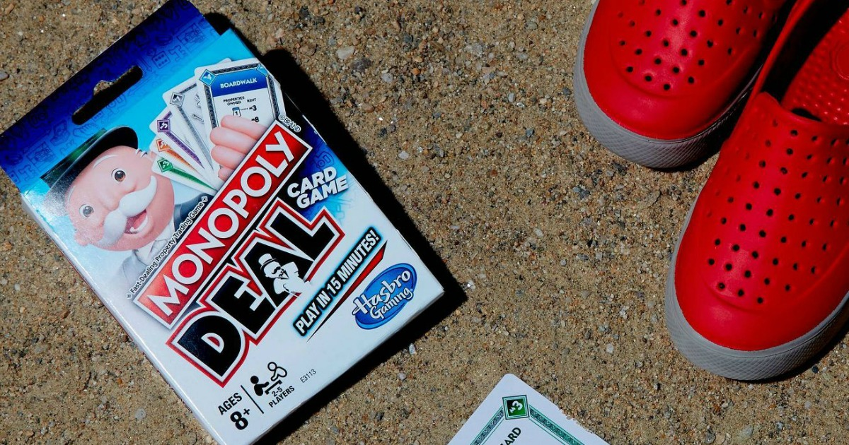 Monopoly Deal Card Game on beach by shoes