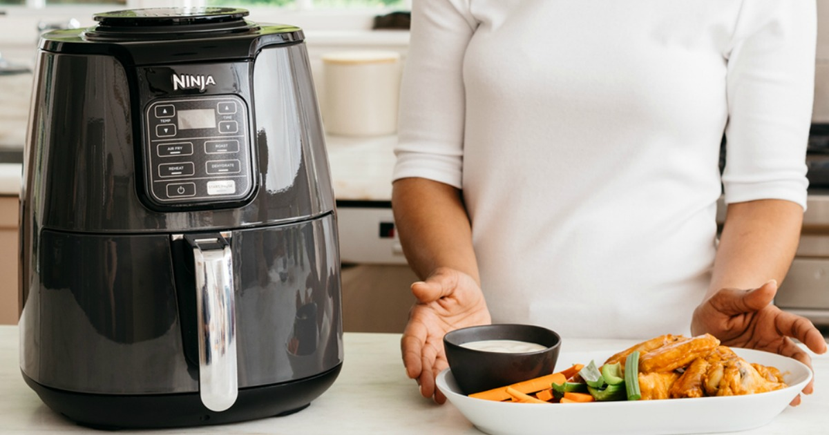 woman with plate of food standing next to a Ninja air fryer