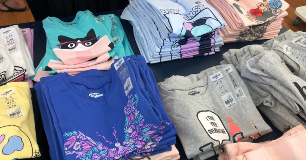 folded oshkosh shirts on table at store
