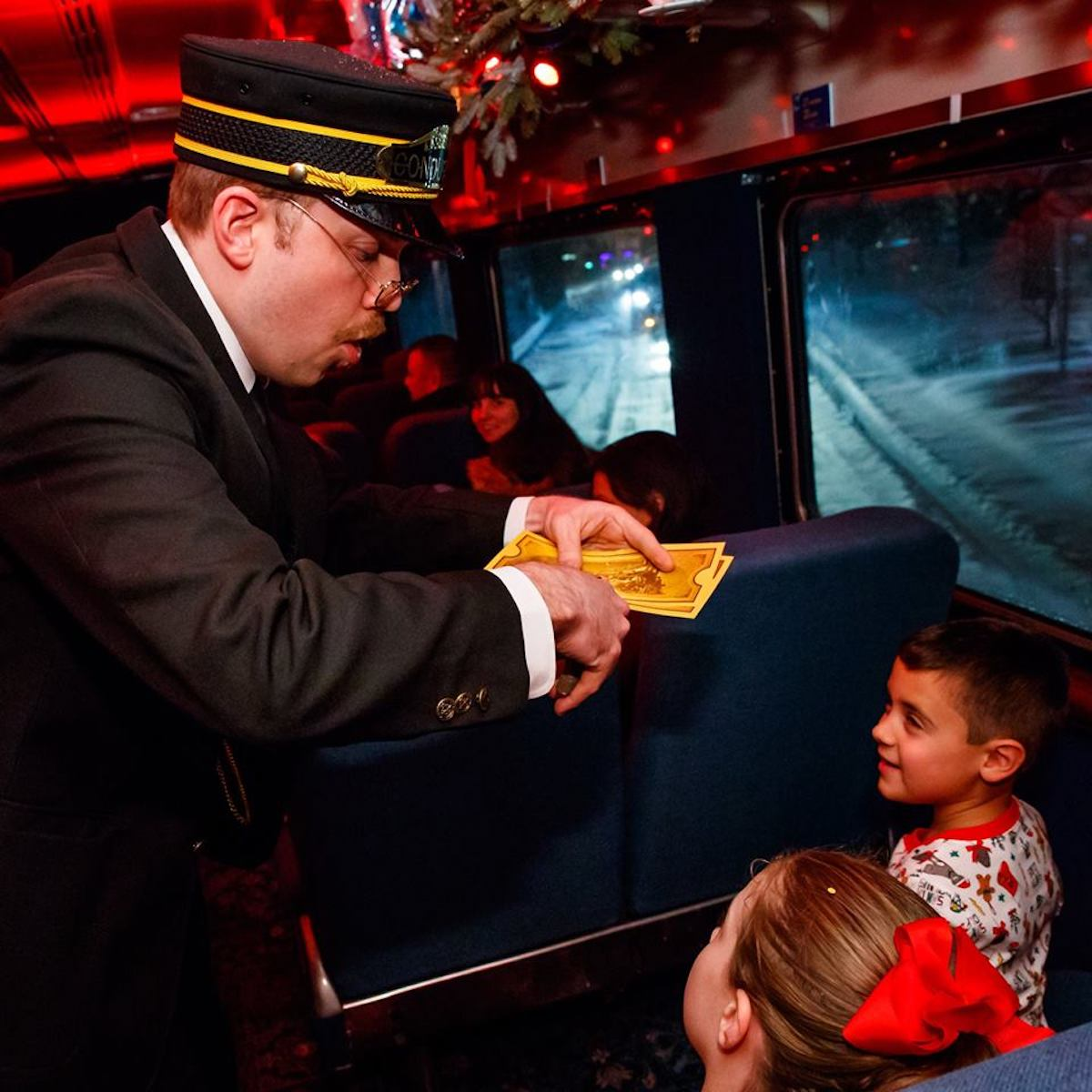 Train conductor clipping ticket on The Polar Express Train