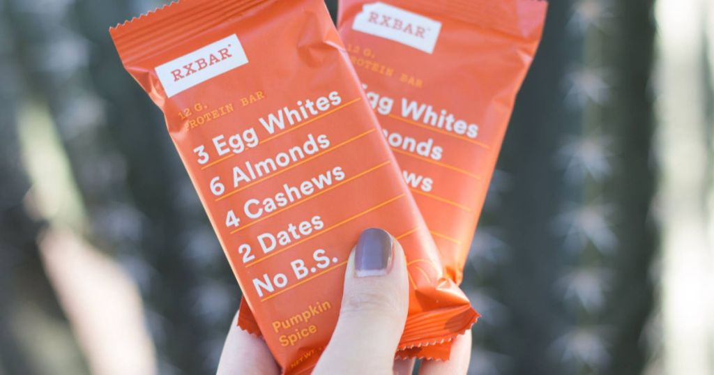 hand holding two pumpkin spice rxbar protein bars