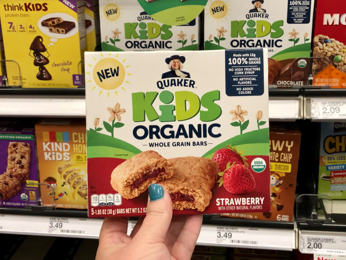 box of Quaker Kids Organic Bars being held in front of a store shelf