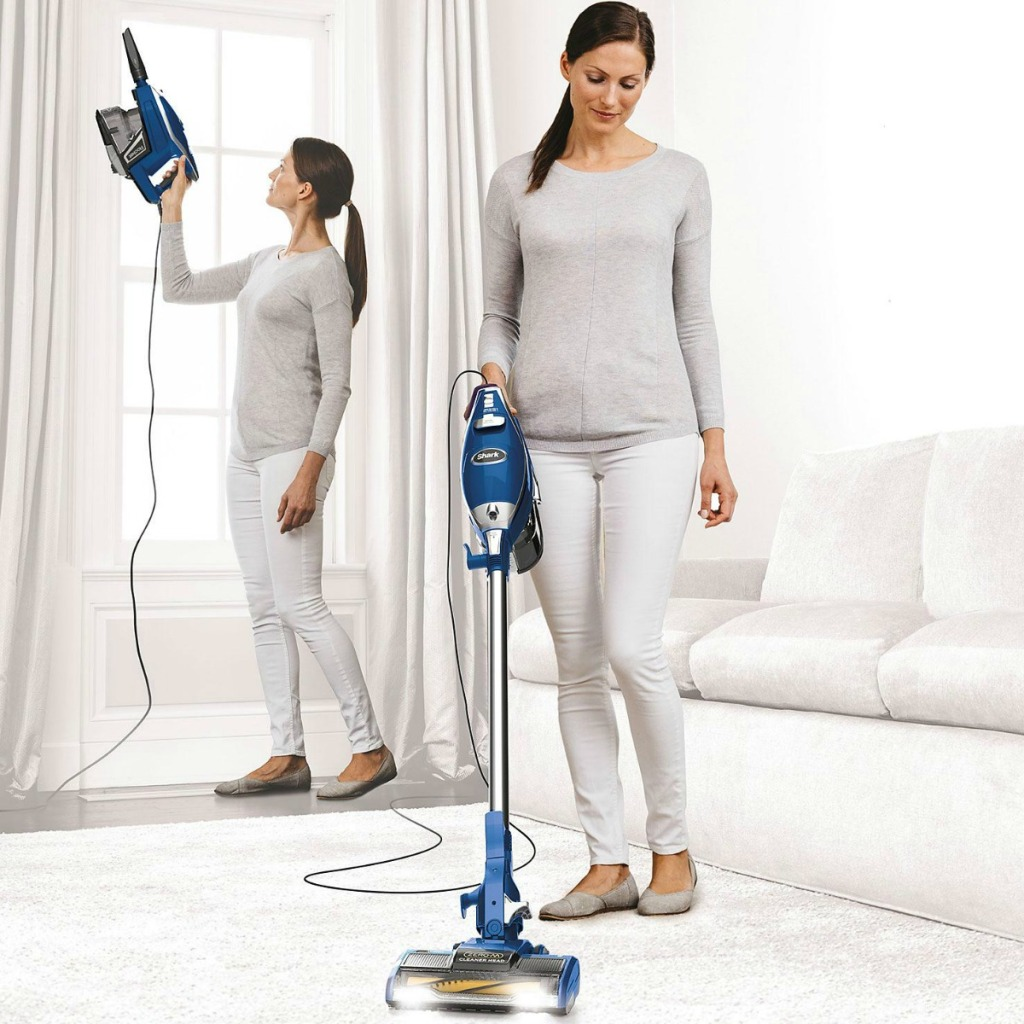 Stick Vacuum Cleaner Woman using corded Shark-brand stick vacuum in living room on carpet and on drapes