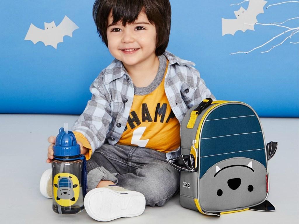boy sittingnext to Skip Hop Bat Backpack