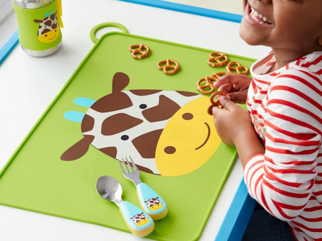 young girl eating snacks off Giraffe food mat
