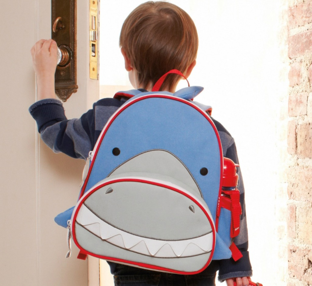 Little boy walking out the front door wearing a Sharked themed Skip Hop Zoo Backpack
