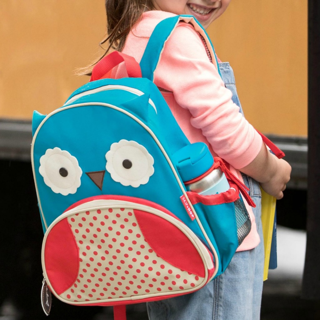 Girl wearing owl themed backpack standing in front of school bus