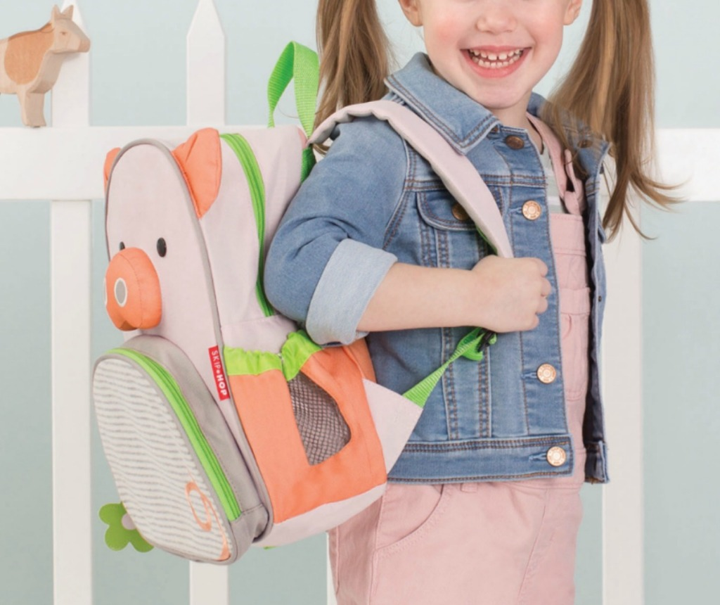 Girl wearing SkipHop brand Pig themed backpack near white picket fence