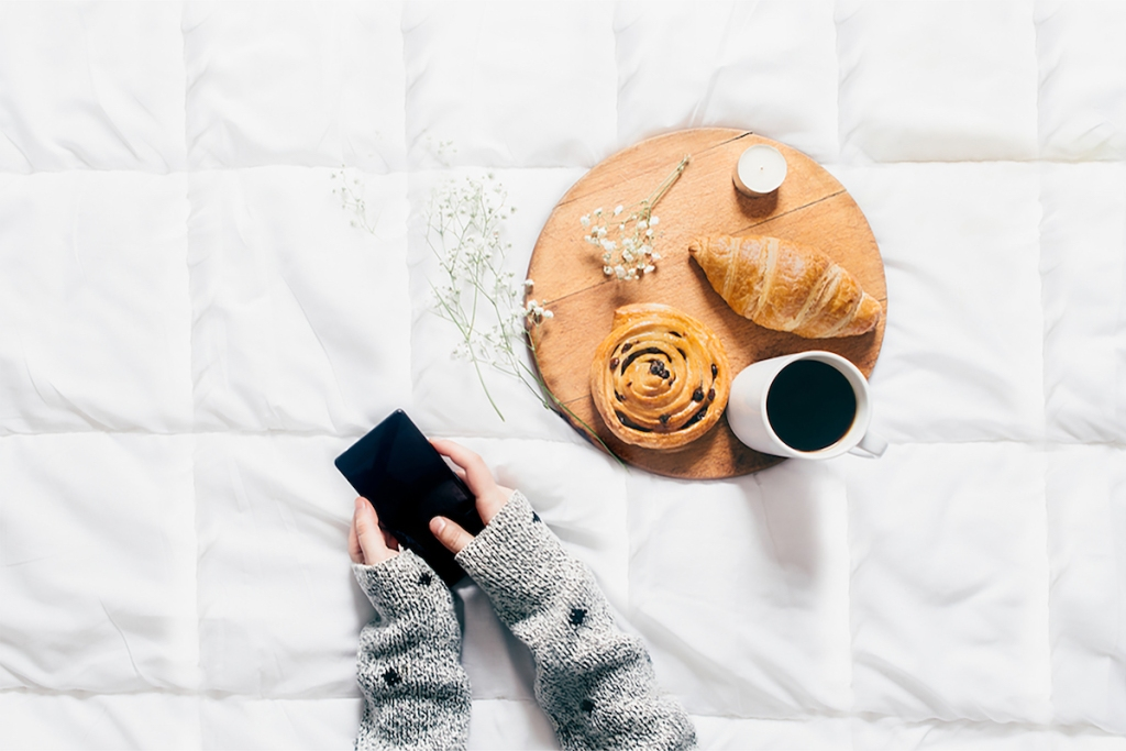 food on bed with person looking at phone