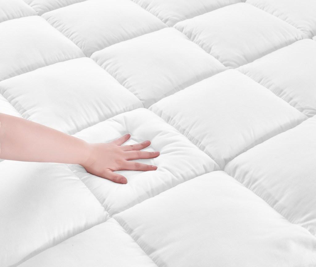 hand on mattress topper