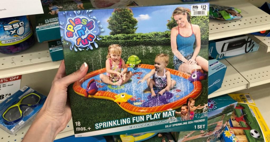 woman holding sprinkling fun play mat box