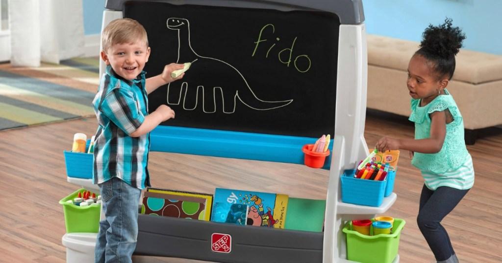 boy and girl drawing on jumbo chalk board