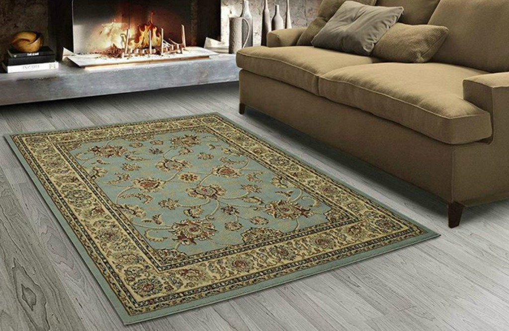 Seafoam green colored area rug with floral print, oriental style on grey hardwood in front of sofa