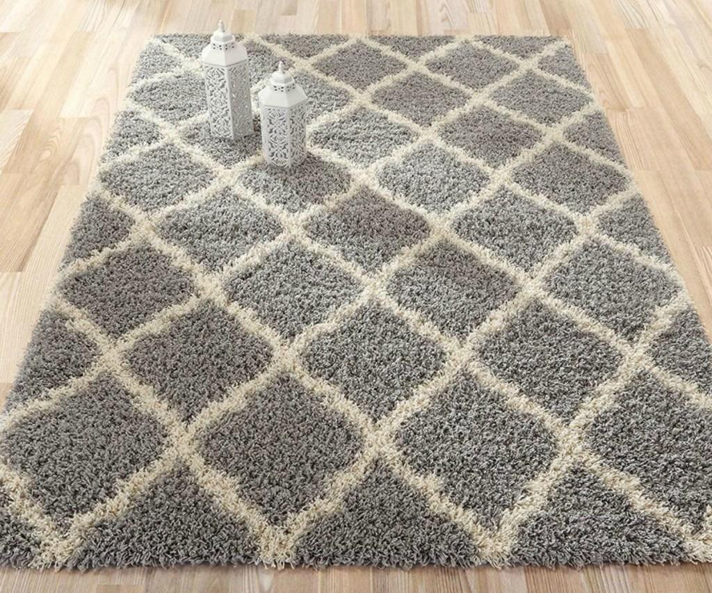 Gray and white printed area rug on hardwood floors with lantern decor