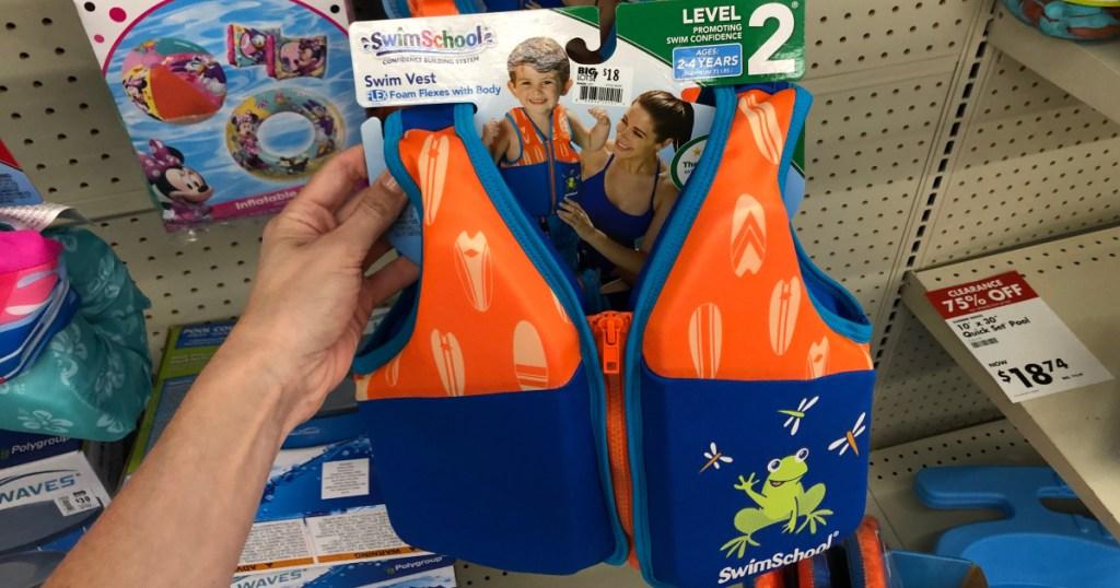 woman holding up swim swchool swim vest