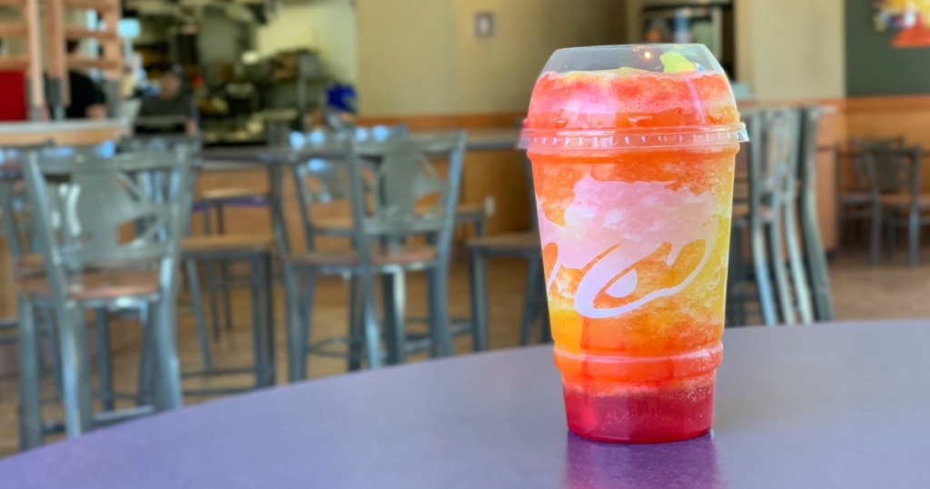 Taco Bell Cherry Sunset Freeze on table inside restaraunt