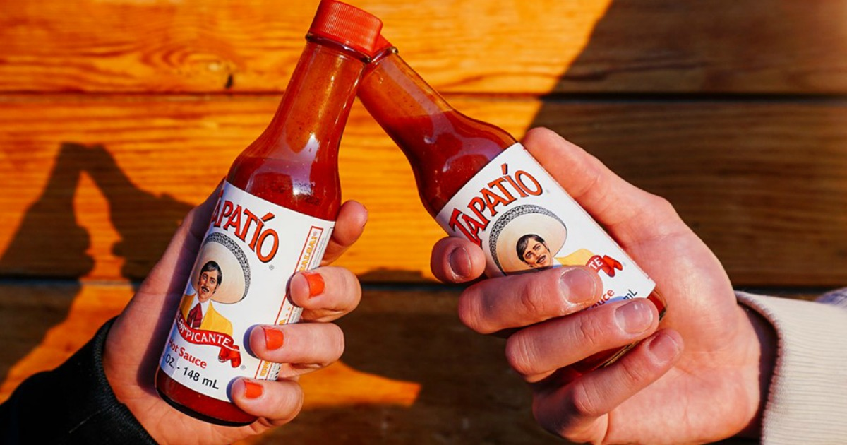 two hands holding a bottle of hot sauce in bad lighting