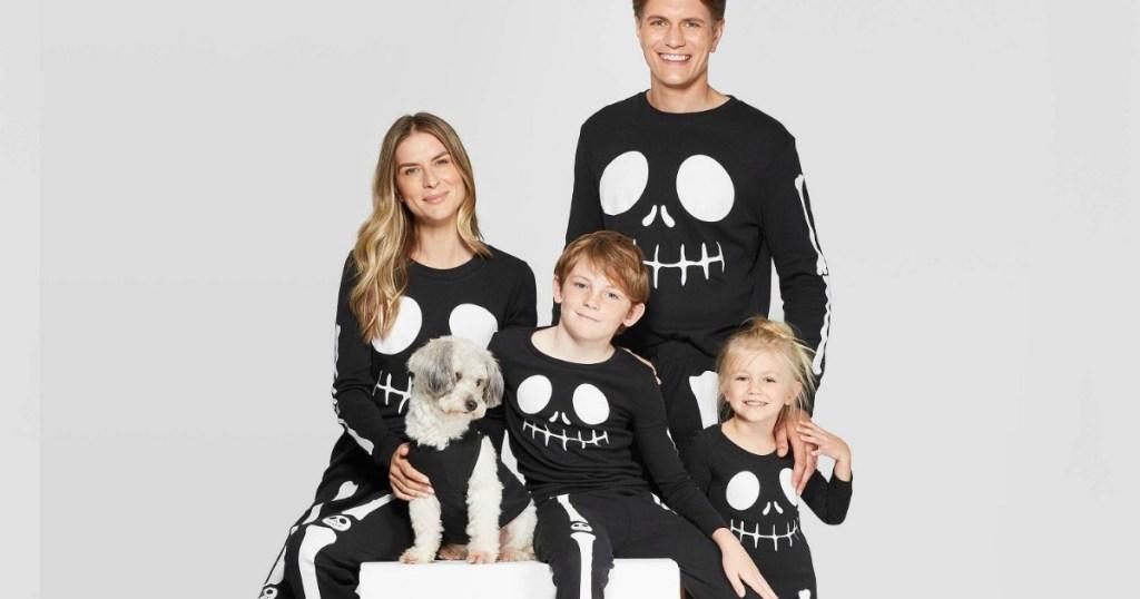Family dressed in matching black Halloween pajamas