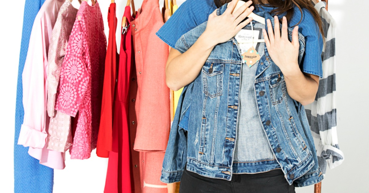 Woman holding up jean jacket with ThredUP tag