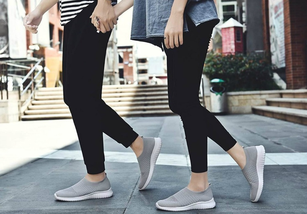 man and woman holding hands while walking and wearing matching gray sneakers