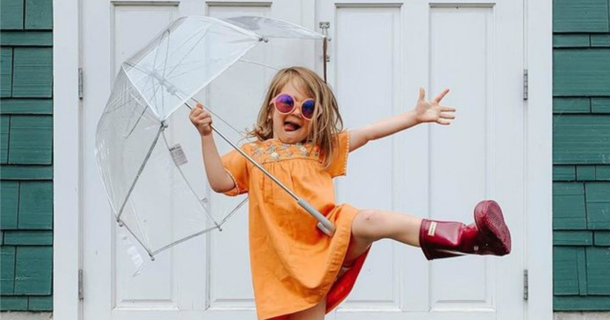 Cute girl holding Totes Bubble Umbrella with oversized rainboots