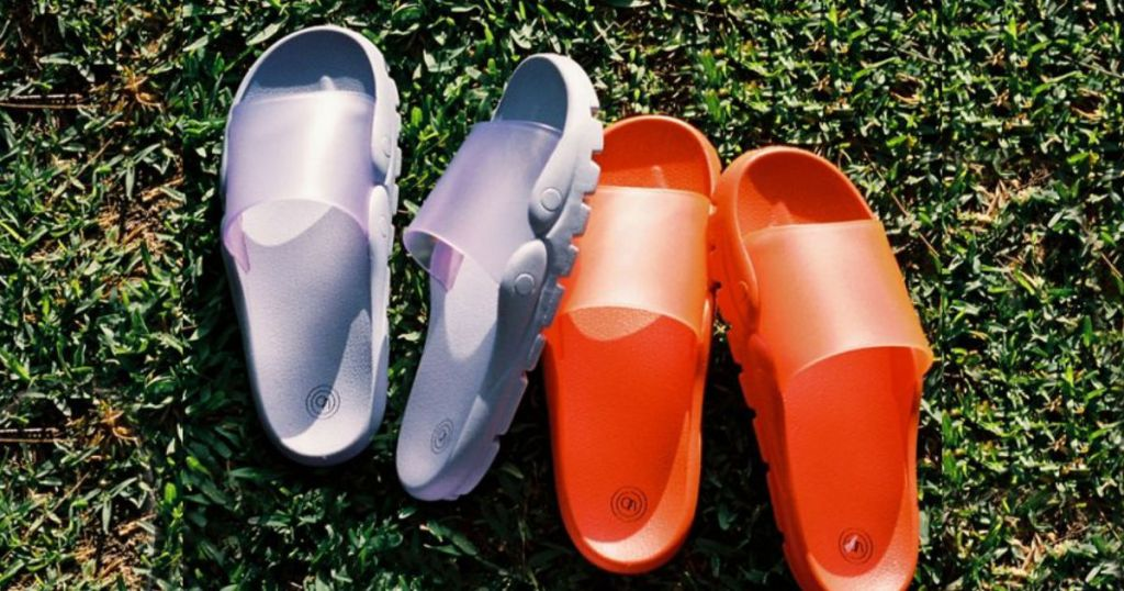 UO Skye Molded Slide Sandals in orange and purple on grass