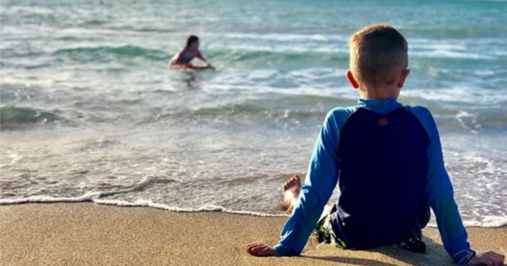 Boy on Beach wearing UV Skinz Boy's Rashguard